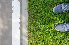 Blue Sneakers on Green Grass Lawn. Blue Sneakers on a Green Grass Stand in Front of an Asphalt Road with a White Dividing Strip Top View Stock Image