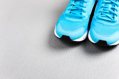 Blue sneakers on grey mat for training. Concept of healthy life, everyday training and force of will Royalty Free Stock Photos