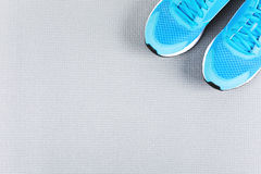 Blue sneakers on grey mat for training. Concept of healthy life, everyday training and force of will Stock Photo