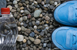 Blue sneakers on pebbles Royalty Free Stock Photos