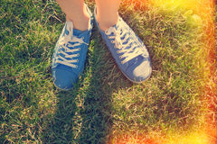 Blue sneakers. On saturated green grass. Photo in old color image style Stock Images