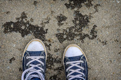 Blue sneakers shoes walking on concrete top view. Blue sneakers shoes walking on old grange dirty concrete top view Stock Photos