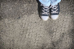Blue sneakers shoes walking on concrete top view. Blue sneakers shoes walking on old grange dirty concrete top view Stock Image