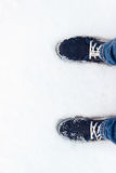 Blue sneakers on snow. A look from above. Royalty Free Stock Image