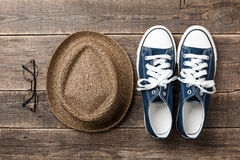 Blue sneakers, straw hat and sunglasses on wooden boards. Top view Stock Images
