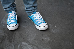 Blue sneakers, teenager feet in gumshoes. Stand on dark gray asphalt. Closeup photo with selective focus and shallow DOF Royalty Free Stock Photo
