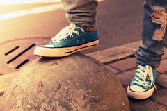 Blue sneakers, teenager feet in gumshoes, toned. Blue sneakers, teenager feet in gumshoes on urban pavement.  Closeup photo with selective focus and warm vintage Stock Photos