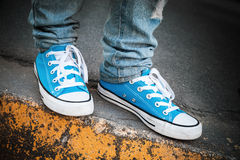 Blue sneakers, teenager feet stands on roadside. Blue sneakers, teenager feet stands on urban roadside. Closeup photo with selective focus and shallow DOF Stock Images