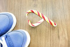 Blue sneakers. wooden background. Candy in the shape of a broken heart. It is expected that you will give up what you like and fro. M an excess lifestyle royalty free stock photography
