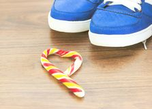 Blue sneakers. wooden background. Candy in the shape of a broken heart. It is expected that you will give up what you like and fro. M an excess lifestyle stock image