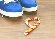 Blue sneakers. wooden background. Candy in the shape of a broken heart. It is expected that you will give up what you like and fro. M an excess lifestyle stock photo