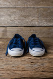 Blue sneakers on wooden background with copy space. Royalty Free Stock Photos