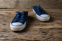 Blue sneakers on wooden background with copy space. A pair of canvas shoes, Blue sneakers on wooden background with copy space.  Vintage effect Stock Image