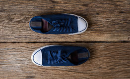 Blue sneakers on wooden background with copy space. A pair of canvas shoes, Blue sneakers on wooden background with copy space.  Vintage effect. Top view Royalty Free Stock Photography