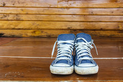 Blue sneakers on the wooden floor Royalty Free Stock Image