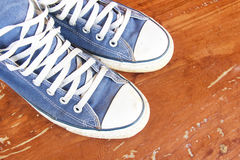 Blue sneakers on the wooden floor Royalty Free Stock Images