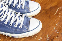 Blue sneakers on the wooden floor Royalty Free Stock Photo