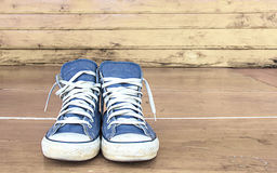 Blue sneakers on the wooden floor, vintage Royalty Free Stock Photos