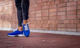 Blue sneakers worn by a teenager. Sneakers on the feet of a girl walking down the street Stock Images