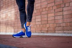Blue sneakers worn by a teenager. Sneakers on the feet of a girl walking down the street Stock Photos