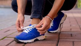 Blue sneakers worn by a teenager. Sneakers on the feet of a girl walking down the street Royalty Free Stock Photo