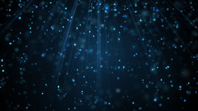 Blue snow particles falling in light rays Royalty Free Stock Image