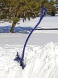 Blue Snow Shovel in Snow Stock Images