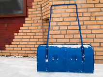 Blue snow shovel  during snowy day, winter time Royalty Free Stock Photography