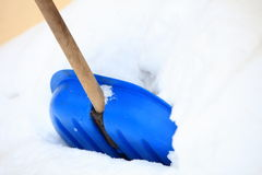 Blue snow shovel standing up in deep snow Stock Photo