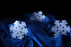 Blue snowflake. Christmas snowflake on blue textile Royalty Free Stock Image