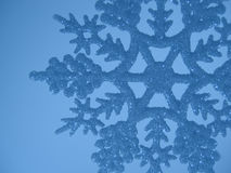 Blue snowflake background. Blue snowflake detail against a blue background Stock Image