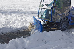 Blue snowplow removing snow. From sidewalk and sprinkled salt antifreeze Royalty Free Stock Photo