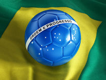 Blue soccer ball on Brazil flag Stock Photos