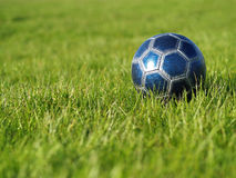 Blue Soccer Ball on Grass. A blue soccer ball on a field of green grass on a bright, sunny day Stock Photography