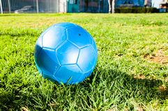 Blue soccer ball. On green field Royalty Free Stock Image