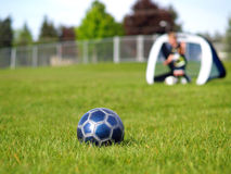 Blue Soccer Ball and Players. A blue soccer ball on field of green grass on a sunny day with kids in the background Stock Photo