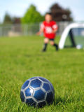 Blue Soccer Ball and Players. A blue soccer ball on field of green grass on a sunny day with kids in the background Royalty Free Stock Images