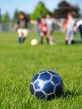 Blue Soccer Ball and Players. A blue soccer ball on field of green grass on a sunny day with kids in the background Royalty Free Stock Photography