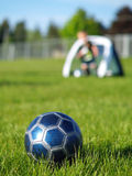 Blue Soccer Ball and Players. A blue soccer ball on field of green grass on a sunny day with kids in the background Stock Images