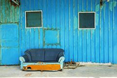 Blue sofa. Old abandoned house front with blue sofa Royalty Free Stock Image