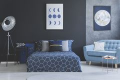 Blue sofa in bedroom interior. With navy blue bed against dark wall with gallery of posters Stock Photo