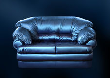 Blue sofa on a black. Background Royalty Free Stock Photos