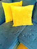 Blue sofa with bright yellow cushions Stock Photography