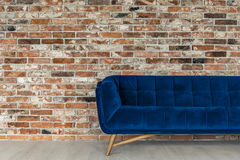 Blue sofa in the loft. Comfortable modern blue sofa in stylish loft with red brick wall stock image