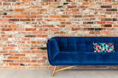 Blue sofa with patchwork pillow. Red brick wall and blue sofa with patchwork pillow stock photo