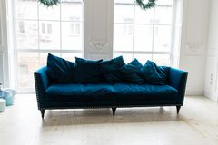 Blue sofa in white simple living room. Modern color of blue velvet couch Royalty Free Stock Images