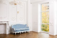 Blue soft sofa in light interior with fabric upholstery. Elegant royal luxury interior with white walls and blue sofa stock images