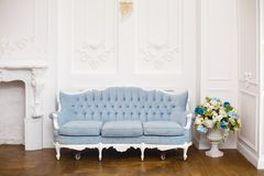 Blue soft sofa in light interior with fabric upholstery. Elegant royal luxury interior with white walls and blue sofa royalty free stock photography
