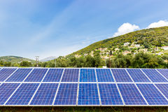 Blue solar collectors near town on mountain Royalty Free Stock Images