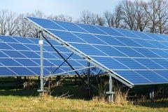 Blue solar panels photovoltaics power station with trees in background. Blue solar panels in photovoltaics power station farm with trees in background, future Royalty Free Stock Photos